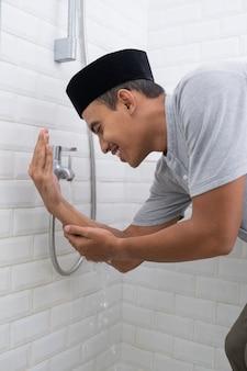 Retrato de joven musulmán realizar la ablución (wudhu) antes de la oración en casa. limpiar su mano