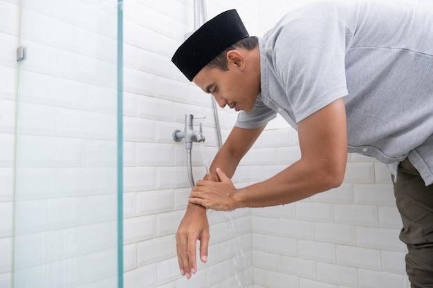 Retrato de joven musulmán realizar la ablución (wudhu) antes de la oración en casa