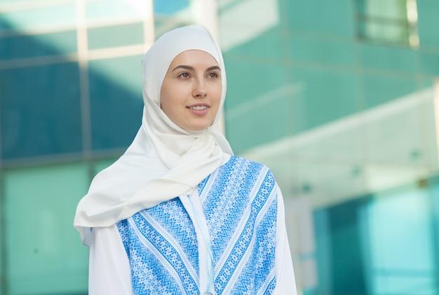 Retrato de joven musulmana con bufanda mientras piensa al aire libre
