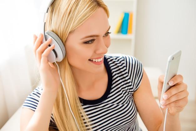 Retrato de joven muy alegre escuchando música en auriculares