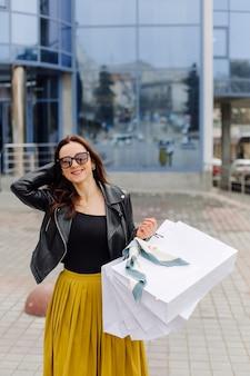 Retrato de joven muy elegante sosteniendo las bolsas de la compra y mirando hacia adelante de buen humor. compras ideales.