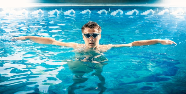 Retrato de joven nadador tomando un respiro y relajándose en la piscina