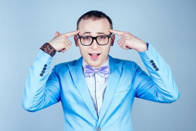 Retrato de un joven nerd gay con gafas, con un elegante traje y corbata piensa