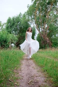 Retrato de joven novia bonita en vestido de novia blanco al aire libre corriendo hacia