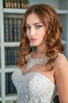 Retrato de una joven novia, hermoso maquillaje y rizos.