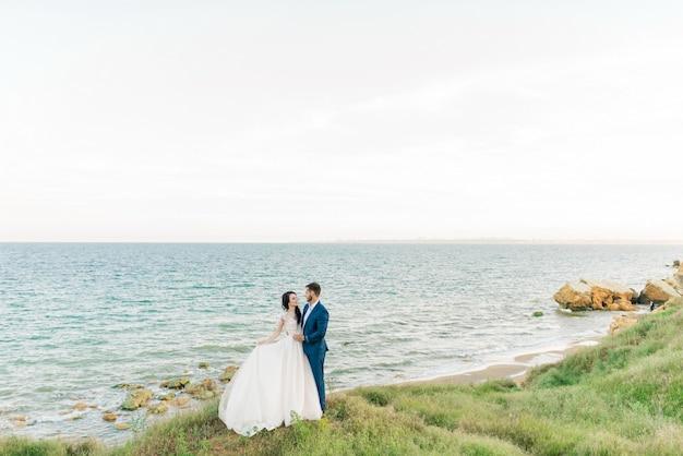 Retrato de la joven novia y el novio de la boda con ramo posando junto a la catedral vieja. pareja de luna de miel besándose en el día de la boda, feliz pareja de enamorados, beso de boda