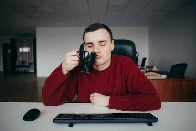 Retrato de un joven oficinista cansado sentado con los ojos cerrados y con una taza de café en la mano.