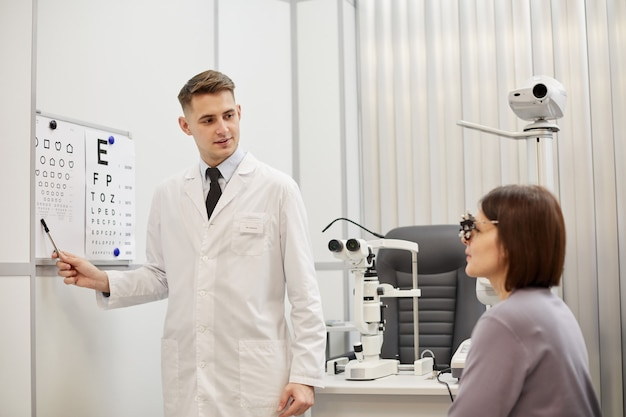 Retrato de joven optometrista apuntando a la tabla de visión