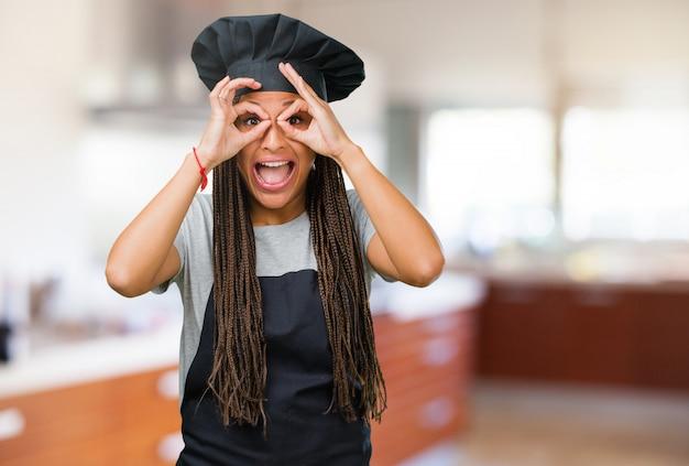 Retrato de una joven panadera negra alegre y confiada haciendo un gesto aceptable, emocionada y gritando, concepto de aprobación y éxito