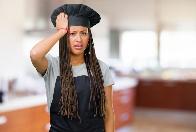 Retrato de una joven panadera negra preocupada y abrumada, olvidadiza, realiza algo