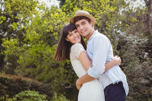 Retrato de joven pareja abrazados en el jardín