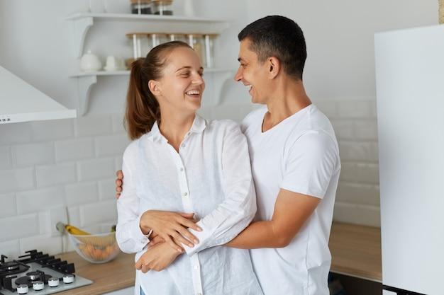 Retrato de joven pareja abrazándose en casa con cocina en segundo plano, marido y mujer mirándose con amor y riendo, felices de quedarse solos en casa y pasar tiempo juntos.