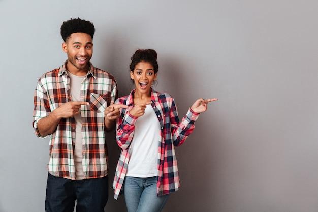 Retrato de una joven pareja africana feliz de pie juntos señalando el lado con los dedos