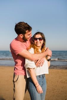 Retrato de una joven pareja amorosa de pie en la playa contra el cielo azul