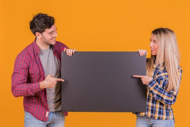 Retrato de una joven pareja apuntando con su dedo en un cartel negro en blanco sobre un fondo naranja