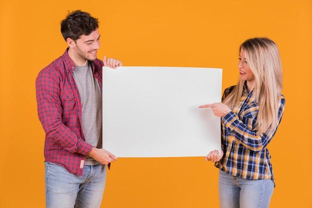 Retrato de una joven pareja apuntando sus dedos en el cartel blanco sobre un fondo naranja