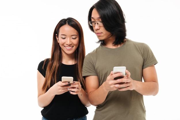 Retrato de una joven pareja asiática casual utilizando teléfonos móviles