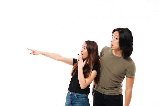 Retrato de una joven pareja asiática sorprendida señalando