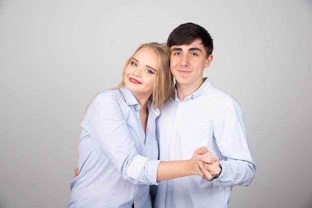 Retrato de una joven pareja bailando y posando en la pared gris.