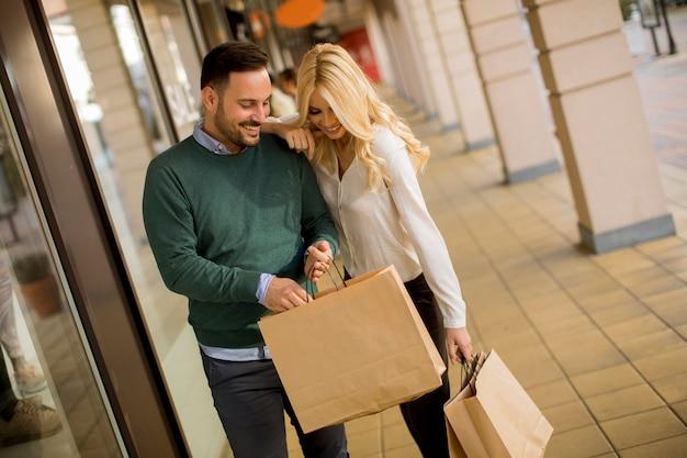 Retrato de joven pareja con bolsas de compras en la ciudad