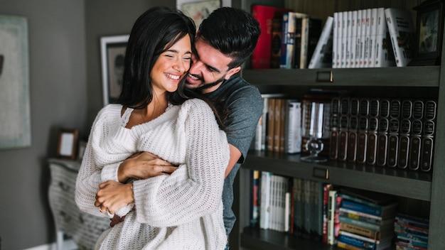 Retrato de la joven pareja cariñosa frente a la estantería