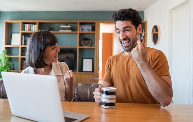 Retrato de joven pareja de compras en línea con una tarjeta de crédito y una computadora portátil desde casa. concepto de comercio electrónico