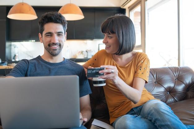 Retrato de joven pareja de compras en línea con una tarjeta de crédito y una computadora portátil desde casa.
