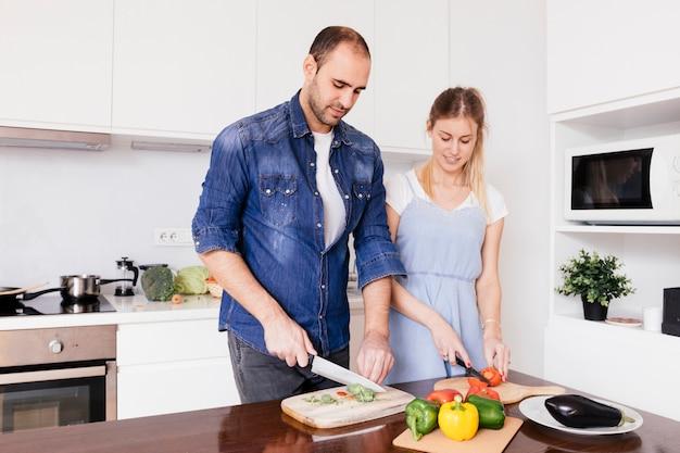 Retrato de joven pareja cortando la campana con cuchillo