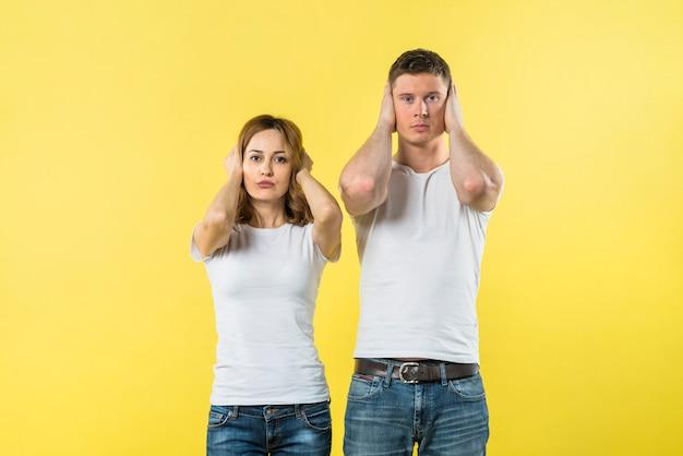 Retrato de joven pareja cubriendo sus orejas contra fondo amarillo
