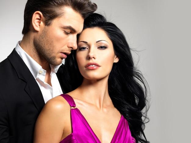 Retrato de joven pareja enamorada posando en el estudio vestida con ropa clásica
