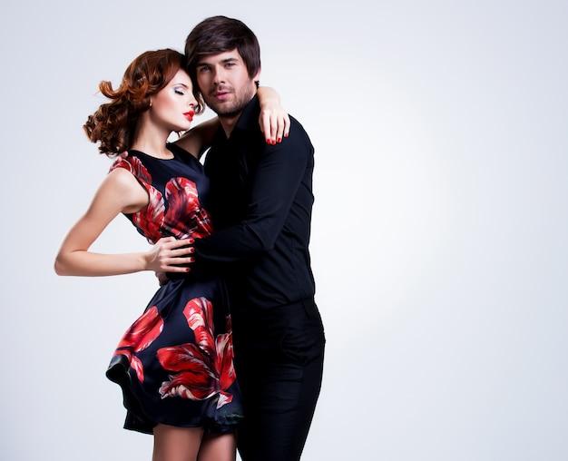 Retrato de joven pareja enamorada posando vestida con ropa clásica
