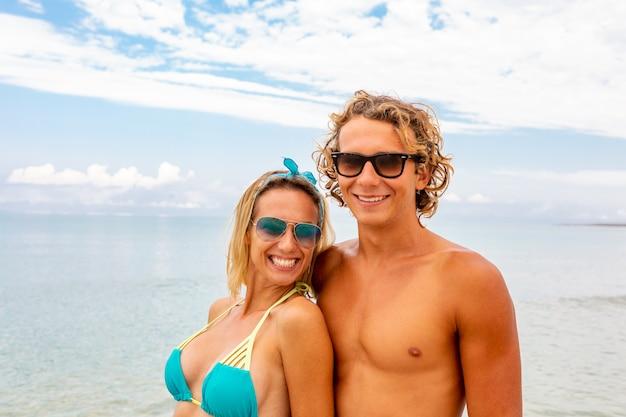 Retrato de joven pareja de enamorados abrazándose en la playa y disfrutando de estar juntos. cartel artístico idealista para banner publicitario