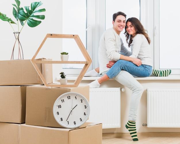 Retrato de la joven pareja encantadora sentada en el alféizar de la ventana en la nueva casa