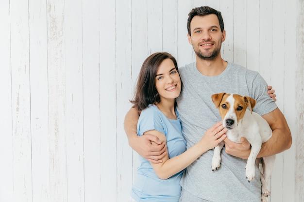 Retrato de joven pareja familiar se abrazan y sostienen a su mascota favorita