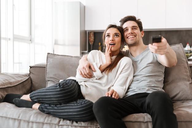 Retrato de una joven pareja feliz descansando en un sofá