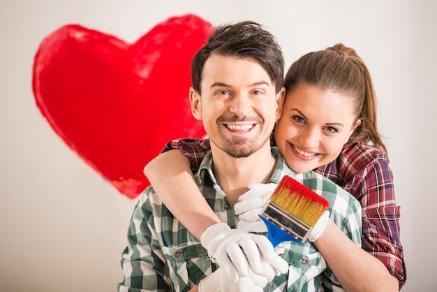 Retrato de joven pareja feliz pintó un corazón.