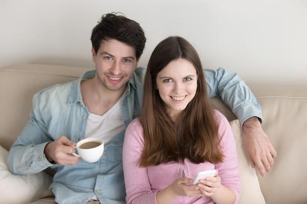 Retrato de joven pareja feliz, relajándose en el interior, disfrutando de café