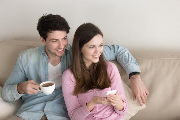 Retrato de la joven pareja feliz relajante en el interior