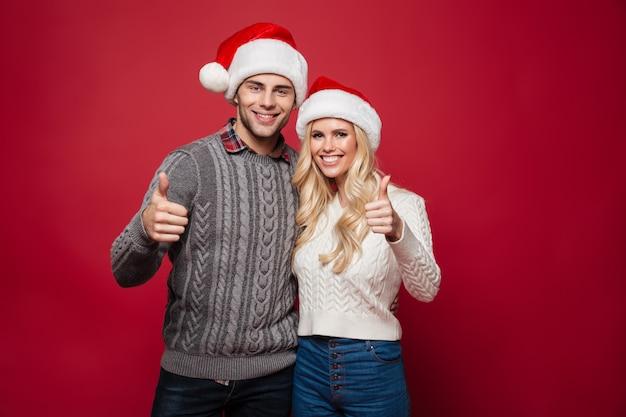 Retrato de una joven pareja feliz en sombreros de navidad