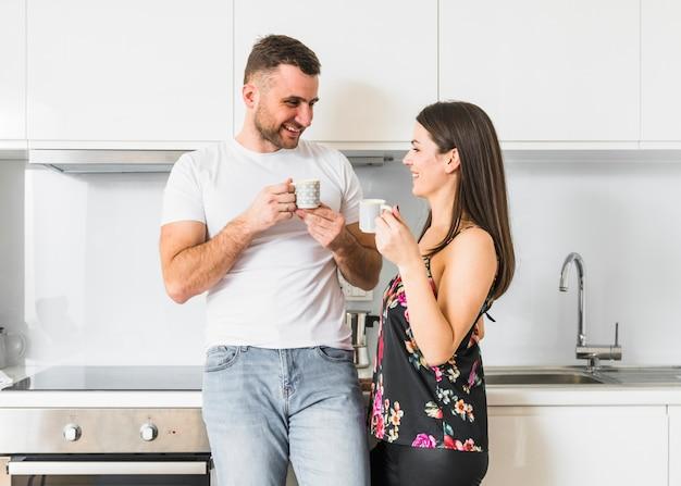 Retrato de una joven pareja feliz sosteniendo la taza de café en la mano mirando el uno al otro en la cocina