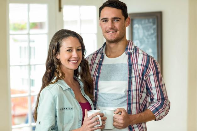 Retrato de la joven pareja feliz tomando una taza de café en la cocina