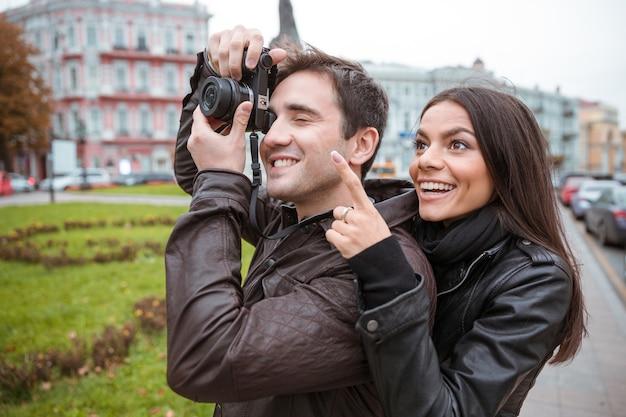 Retrato de una joven pareja feliz viajando y haciendo fotos en el frente en la vieja ciudad europea