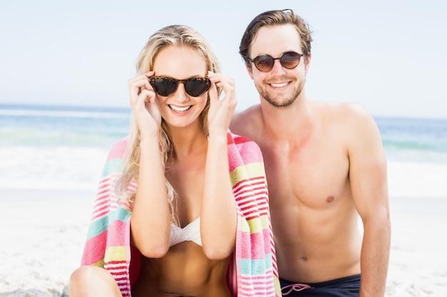 Retrato de joven pareja con gafas de sol en la playa