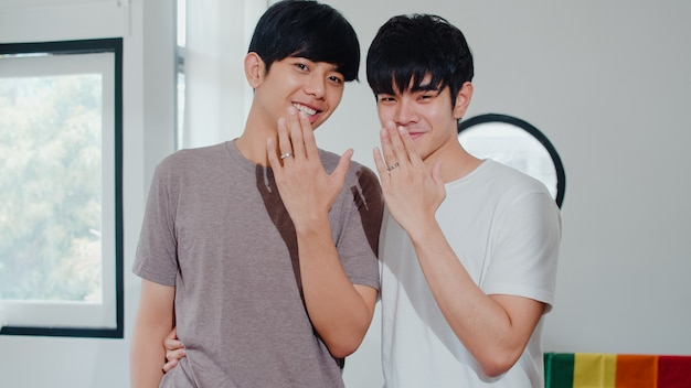 Retrato joven pareja gay asiática sentirse feliz mostrando anillo en casa. los hombres lgbtq + de asia se relajan con una gran sonrisa mirando a la cámara mientras se abrazan en la moderna sala de estar de la casa por la mañana.