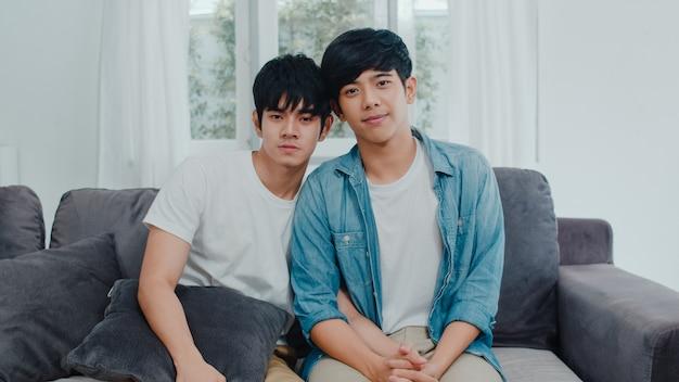 Retrato joven pareja gay asiática se siente feliz sonriendo en casa. los hombres asiáticos lgbtq relajan una sonrisa dentuda mirando a la cámara mientras está acostado en el sofá en la sala de estar en casa por la mañana.