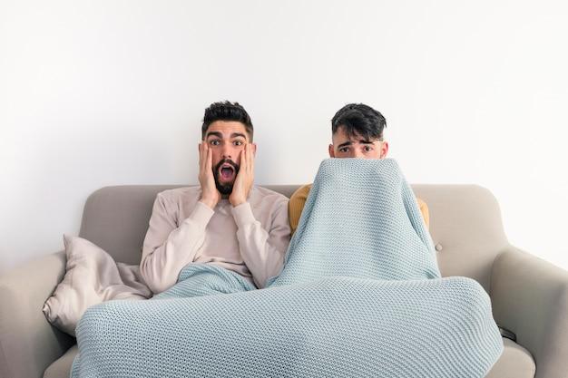 Retrato de joven pareja gay sentada en el sofá viendo una película de terror en la televisión contra una pared blanca
