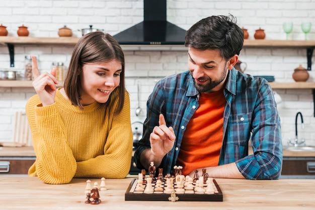 Retrato de una joven pareja jugando al ajedrez en la cocina