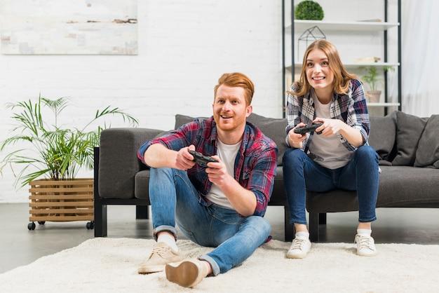 Retrato de joven pareja jugando el videojuego juntos en casa