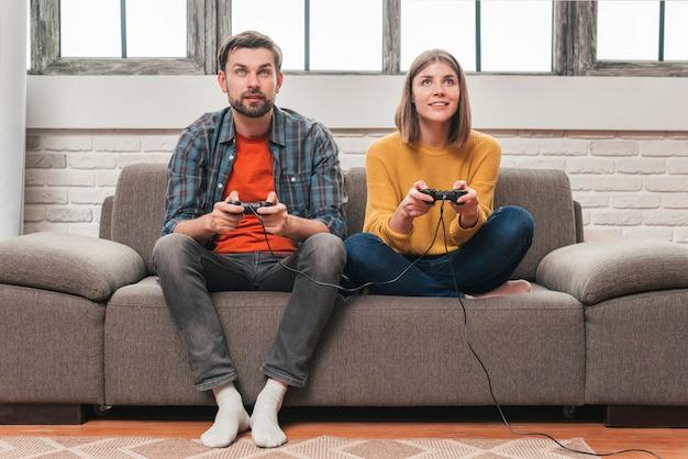 Retrato de una joven pareja jugando videojuegos con joysticks.