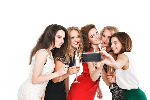 Retrato de una joven pareja de moda chicas rubias y morenas en un vestido brillante posando y sonriendo a la cámara y hace un teléfono inteligente selfi